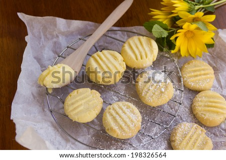 Delicious oven fresh baked melting moments shortbread biscuits with sweet filling and daisies in a rustic setting.