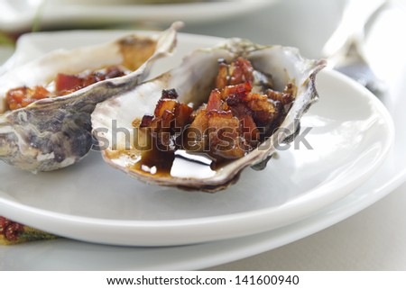 Delicious oysters kilpatrick with bacon and worcestershire sauce ready to serve. - stock photo