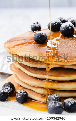 Delicious pancake stack with fresh blueberries and dripping maple syrup - stock photo