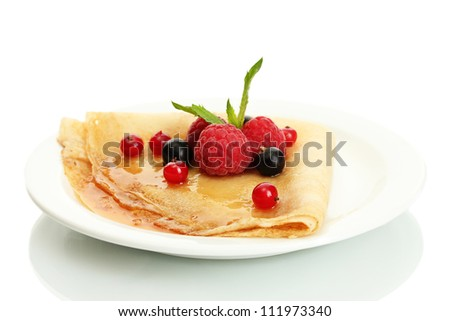 Delicious pancake with berries and honey on plate on wooden table - stock photo