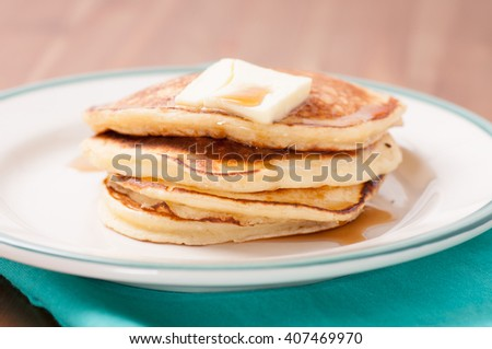 delicious pancakes in a stack with melting butter and maple syrup - stock photo