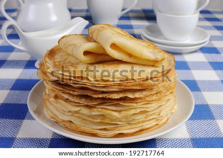 delicious pancakes on a plate with milk sauce - stock photo