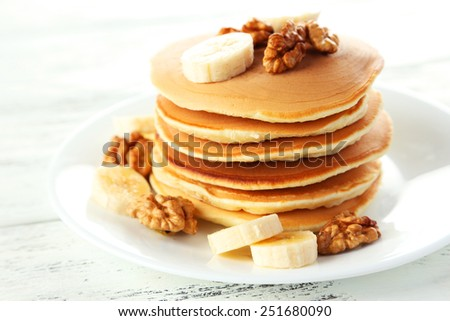 Delicious pancakes with banana on white wooden background - stock photo