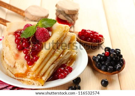 Delicious pancakes with berries, jam and honey on wooden table - stock photo