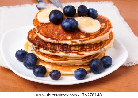 Delicious pancakes with blueberry and bananas on white plate - stock photo
