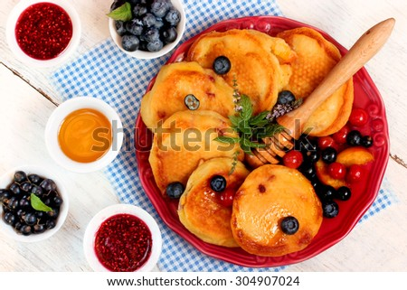 Delicious pancakes with fresh berries, jam and honey - stock photo
