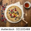 delicious pancakes with fresh berries with honey, almonds cup of tea with honey spoon on white plate with napkin on wooden rustic background top view - stock photo