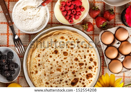 Delicious pancakes with fruit on the kitchen table  - stock photo