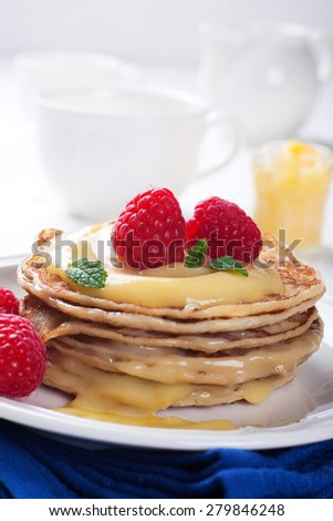 Delicious pancakes with homemade lime curd and fresh raspberries. Selective focus - stock photo