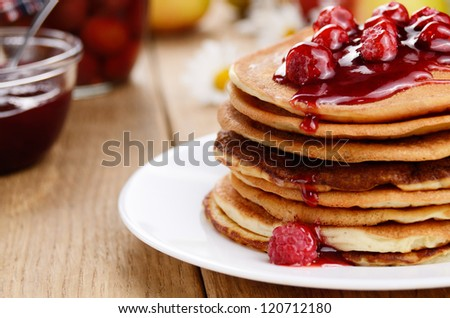 Delicious pancakes with raspberries on the wooden kitchen table - stock photo