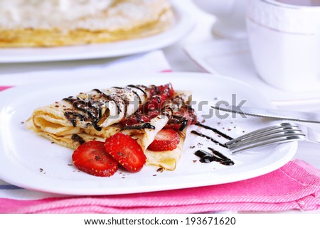 Delicious pancakes with strawberries and chocolate on plate on table - stock photo