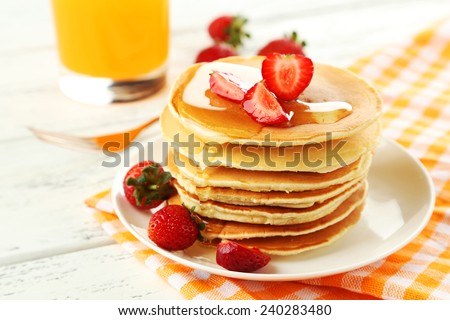 Delicious pancakes with strawberry on white wooden background - stock photo