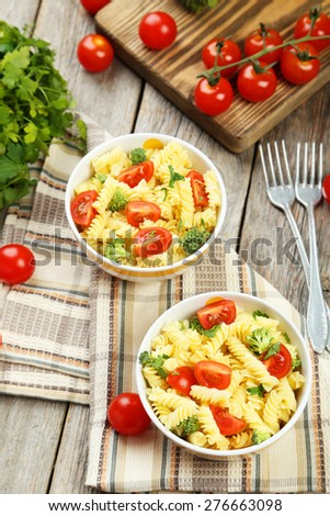 Delicious pasta in bowl on grey wooden background