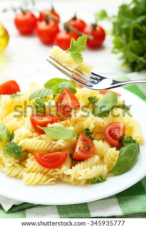 Delicious pasta on plate on white wooden background