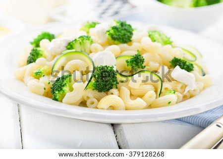 Delicious pasta salad with cheese and broccoli on plate on rustic wooden background, selective focus - stock photo