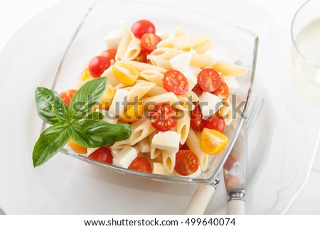 delicious pasta salad with fresh mozarella and cherry tomatoes, basil