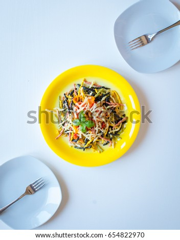 Delicious pasta with fresh vegetables and cheese, on a wooden background . Top view