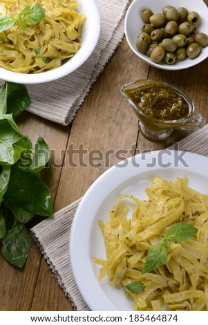 Delicious pasta with pesto on plate on table close-up