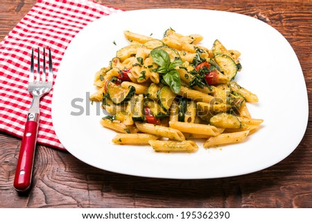 Delicious pasta with sauce,zucchini and tomatoes - stock photo
