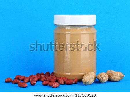 Delicious peanut butter in jar of peanut near on blue background