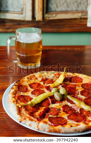 Delicious Peperonie Peperuncino Pizza and Beer Mug on wooden table in a rustic restaurant. Ingredients peeled tomato, cheese, sausage, pepperoni, olives, oregano. - stock photo