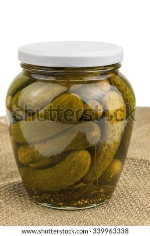 delicious pickled cucumber on burlap napkin - stock photo