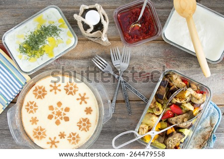 Delicious picnic lunch with grilled vegetables, tzatiki, yogurt with dill, pepper paste and a decorative milky semolina dessert , overhead view on a wooden table - stock photo