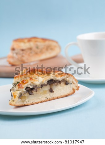 delicious pie with mushrooms in a studio against a blue background with a cup of tea - stock photo