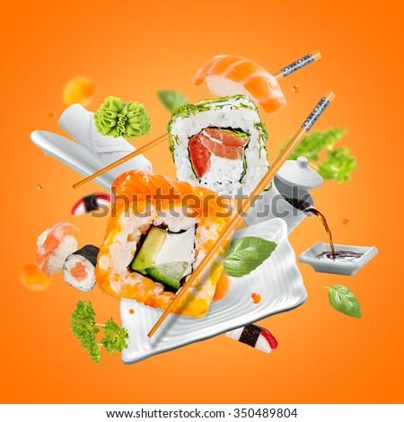Delicious pieces of sushi, isolated on orange background - stock photo