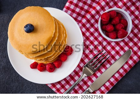 Delicious pile of hot homemade pancakes with fresh raspberries and blueberries on a red and white checkered napkin