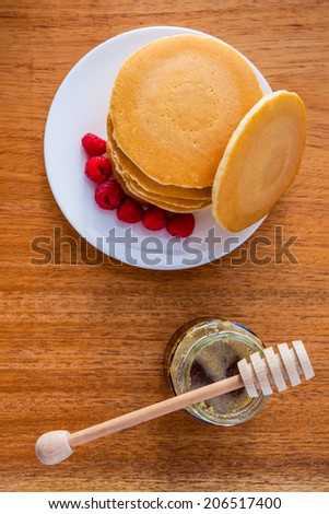Delicious pile of hot homemade pancakes with fresh raspberries and maple syrup
