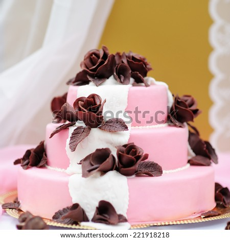 Delicious pink wedding cake decorated with brown cream roses - stock photo