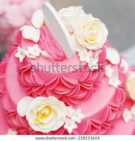 Delicious pink wedding cake decorated with white cream roses - stock photo