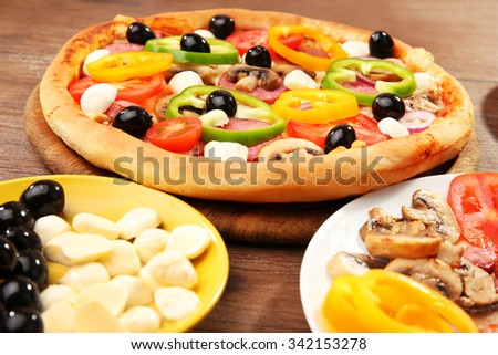 Delicious pizza and ingredients at the restaurant, close-up - stock photo