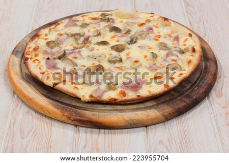 Delicious pizza mushroom with ham on wood table - stock photo