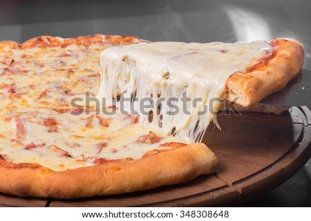 Delicious pizza slice with lot of cheese - stock photo