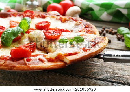 Delicious pizza with cheese and cherry tomatoes on wooden table, closeup - stock photo