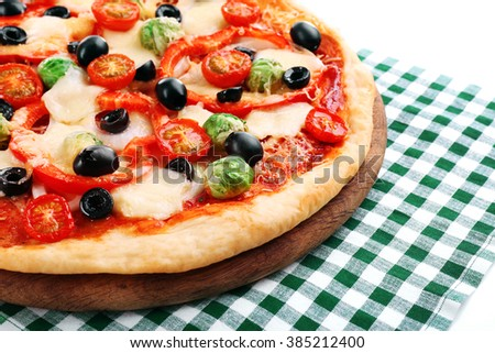 Delicious pizza with cheese and vegetables on green checkered napkin closeup