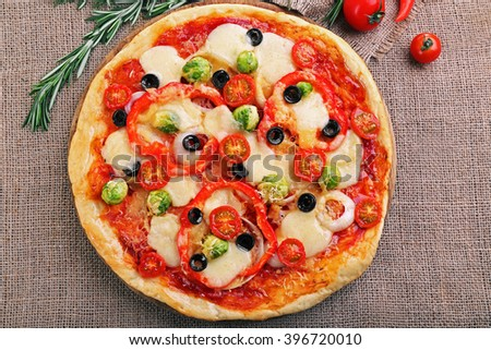 Delicious pizza with cheese and vegetables on sackcloth background