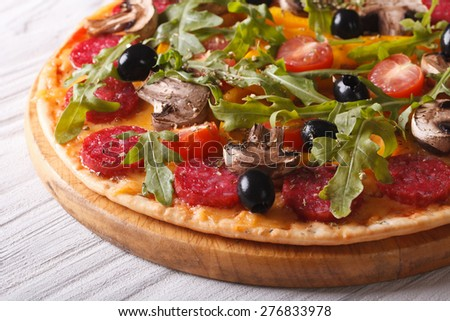 Delicious pizza with herbs, vegetables and salami close up on the table. horizontal  - stock photo