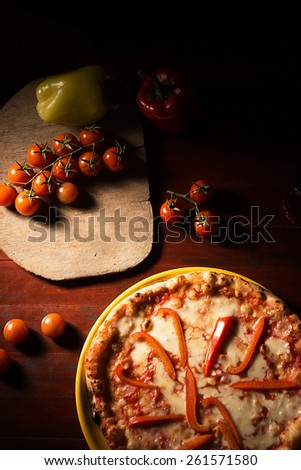 Delicious pizza with mozzarella cheese and pepper on wooden texture - stock photo