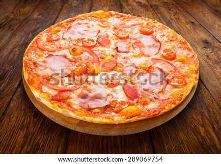 Delicious pizza with peppers, bacon and cherry tomatoes - thin pastry crust isolated at wooden background - stock photo