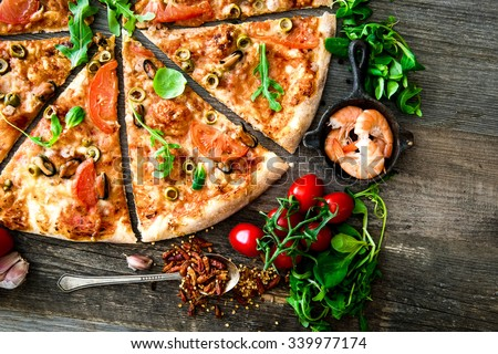 delicious pizza with seafood on wooden table - stock photo