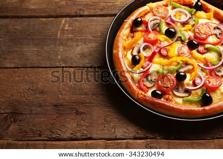 Delicious pizza with vegetables, on wooden table, close-up - stock photo