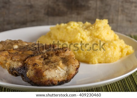 Delicious plate of fried carp with polenta - stock photo