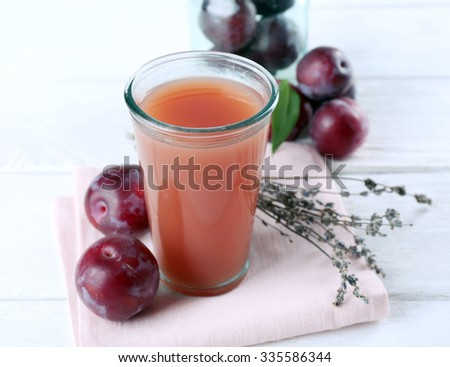 Delicious plum juice with fruits on wooden table close up