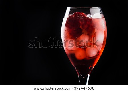 Delicious pomegranate cocktail isolated on black background - stock photo