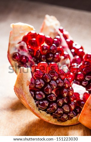 Delicious pomegranate with seeds on wooden board