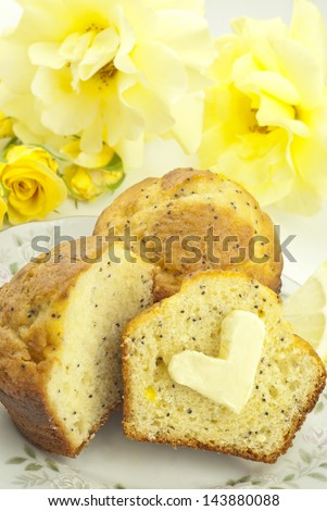 Delicious poppy seed muffins on a plate with heart shaped butter and yellow roses