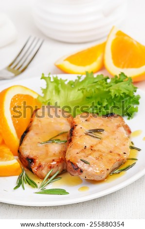 Delicious pork chop with orange sauce on white plate - stock photo